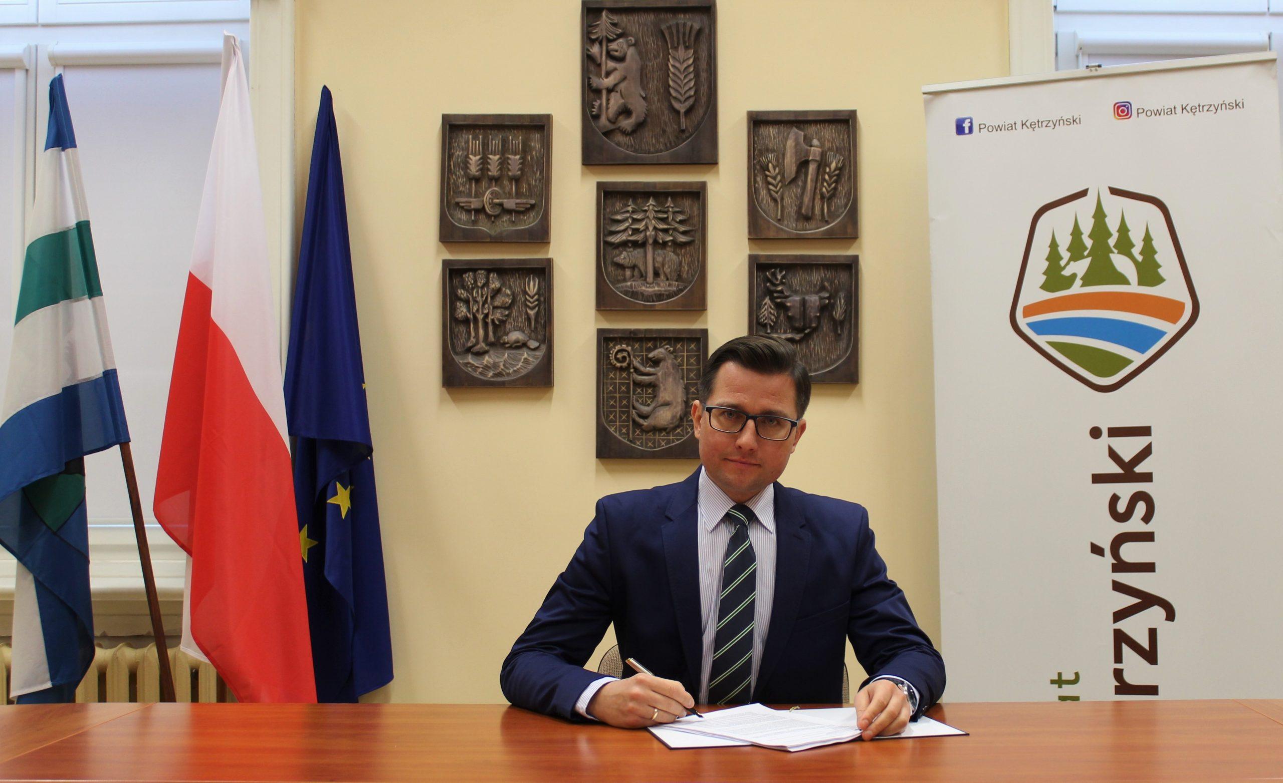 Fotografia przedstawia starostę kętrzyńskiego Michała Kochanowskiego podpisującego umowę na realizację budowy boiska w Reszlu.