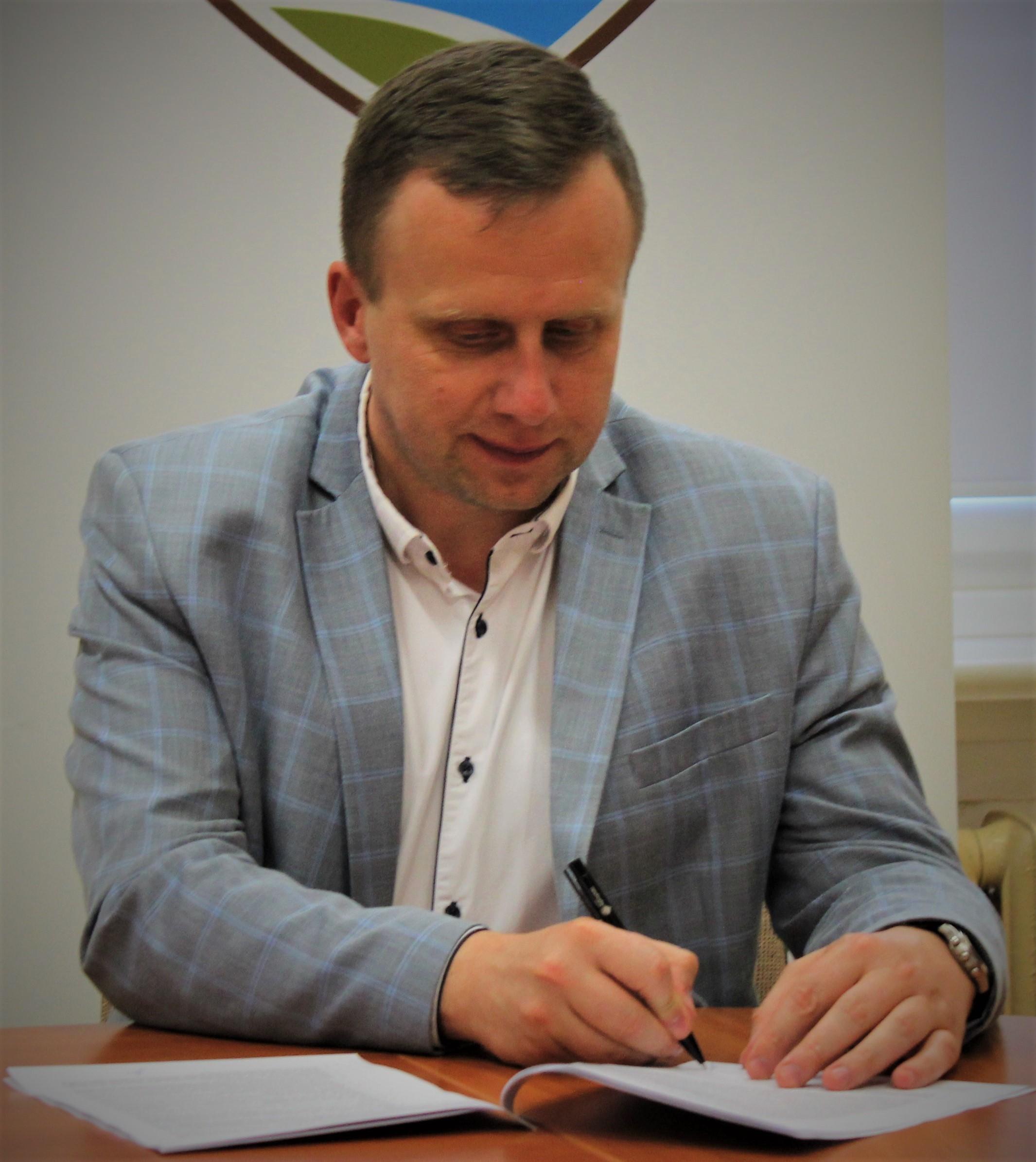 Fotografia przedstawia wicestarostę Andrzeja Lewandowskiego podpisującego umowę o dofinansowanie projektu