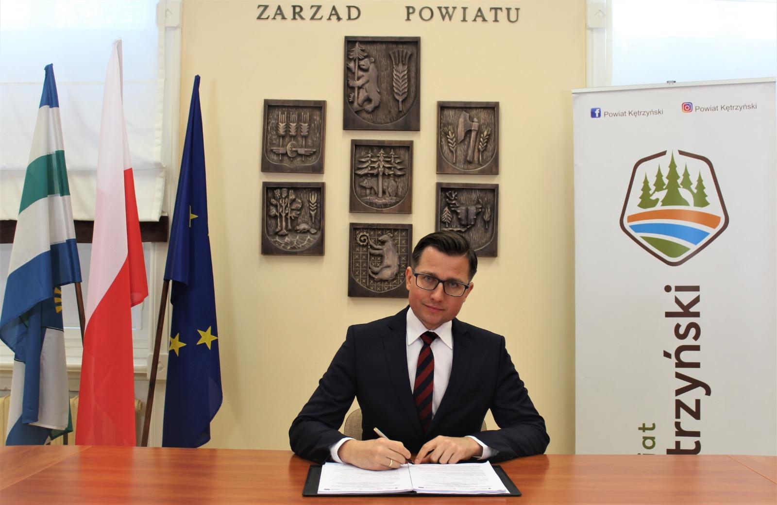 Fotografia przedstawia starostę kętrzyńskiego Michała Kochanowskiego podpisującego umowę o dofinansowanie projektu