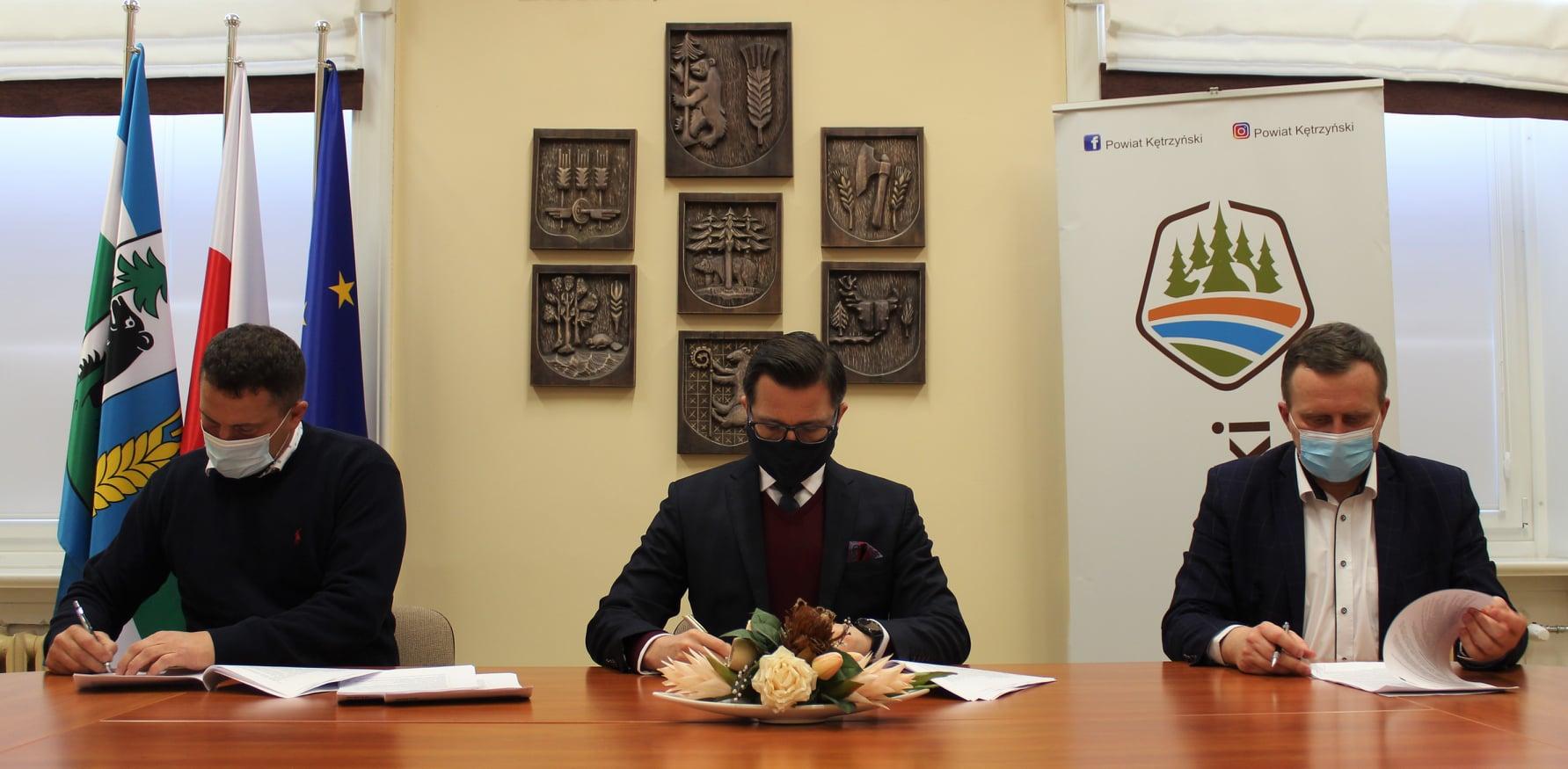 Zdjęcie przedstawia starostę kętrzyńskiego Michała Kochanowskiego, wicestarostę Andrzeja Lewandowskiego oraz wykonawcę inwestycji Karola Szymon Siłkowskiego podpisujących umowę