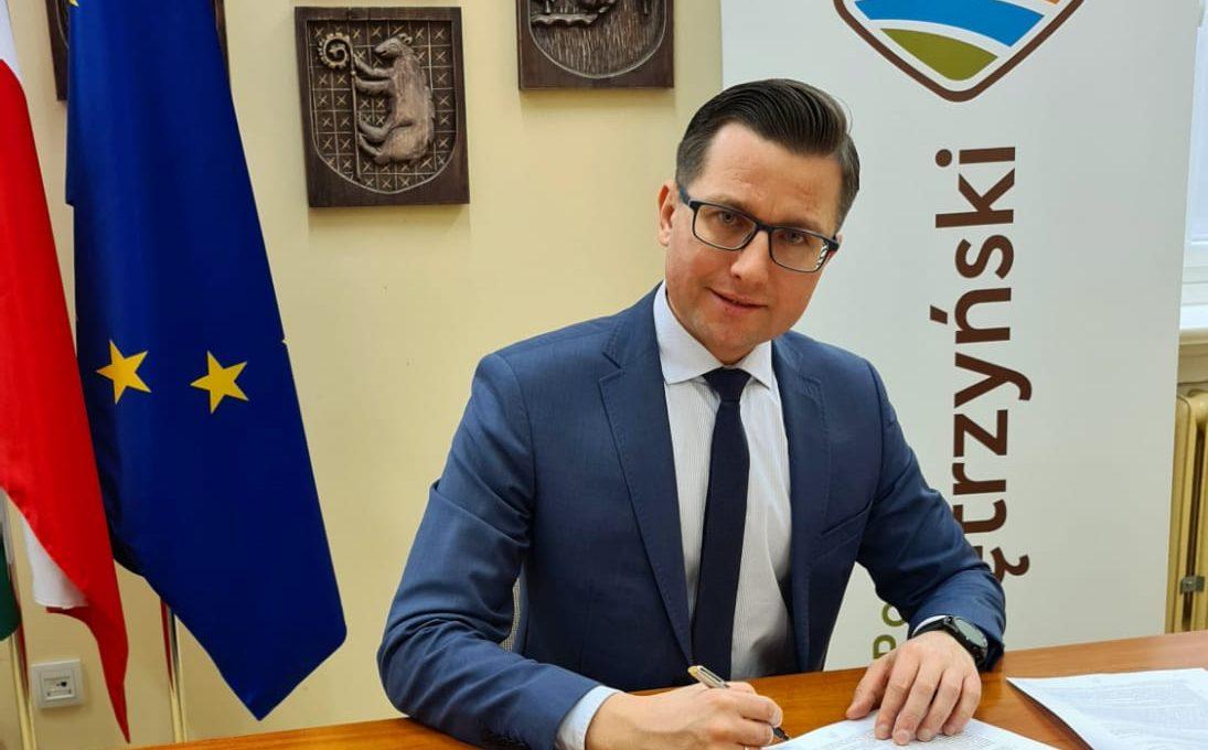Zdjęcie przedstawia starostę kętrzyńskiego Michała Kochanowskiego podpisującego umowę na realizację zadania