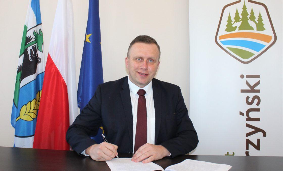 Zdjęcie przedstawia wicestarostę Andrzeja Lewandowskiego podpisującego umowę na realizację zadania