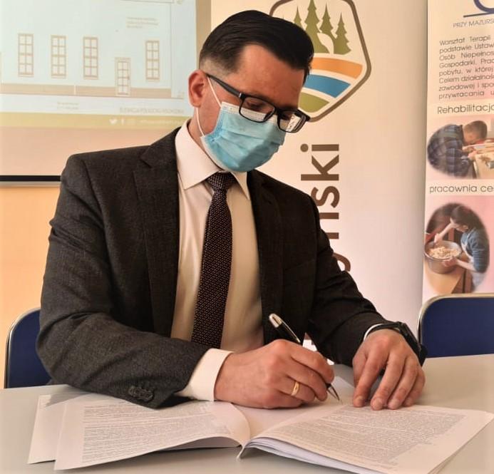 Zdjęcie przedstawia starostę kętrzyńskiego Michała Kochanowskiego podpisującego umowę na budowę Zakładu Aktywności Zawodowej w Kętrzynie
