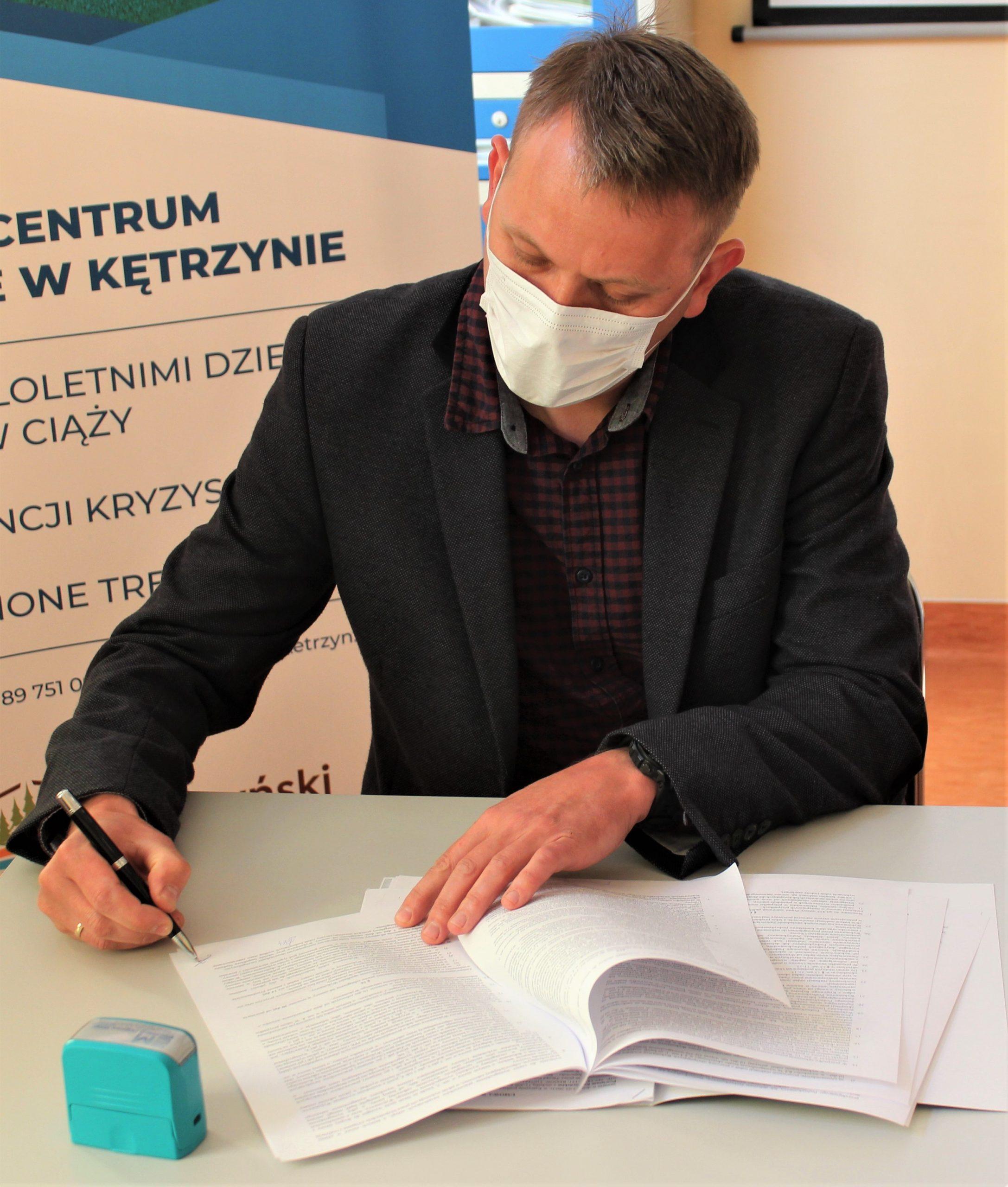 Zdjęcie przedstawia wykonawcę inwestycji podpisującego umowę na budowę Zakładu Aktywności Zawodowej w Kętrzynie