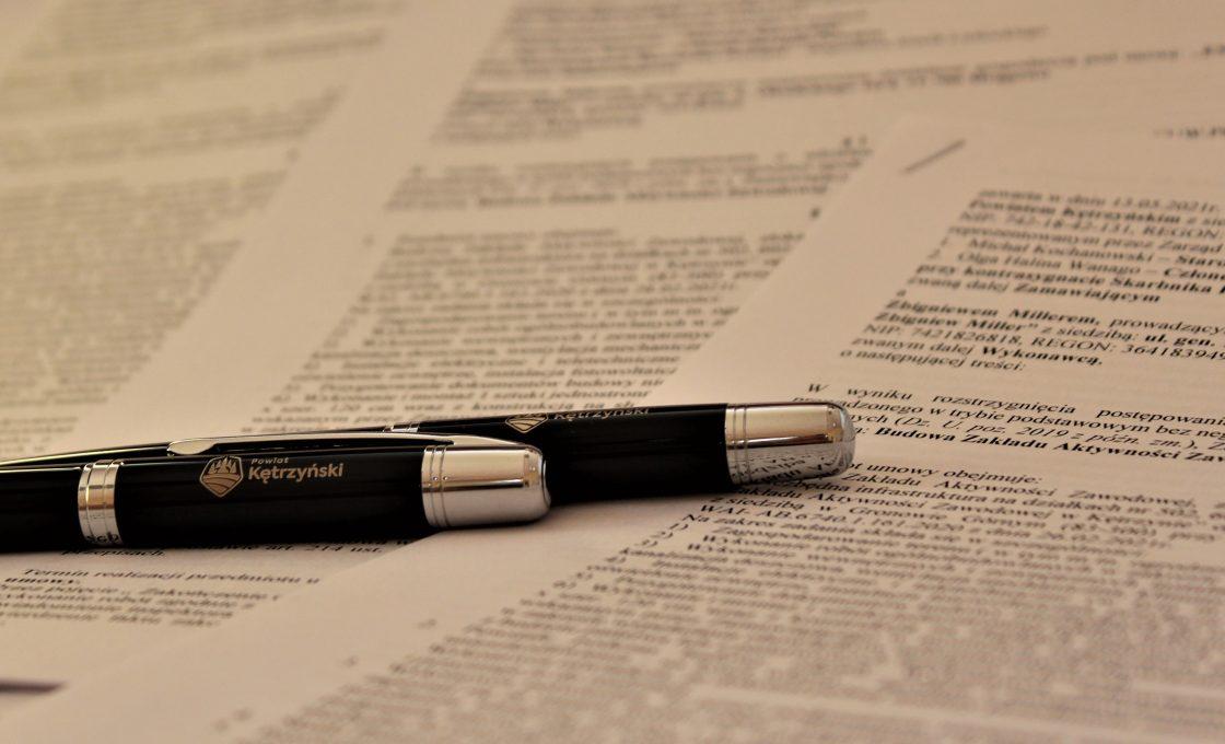 Zdjęcia przedstawia długopis i w tle umowa na budowę Zakładu Aktywizacji Zawodowej  w Kętrzynie