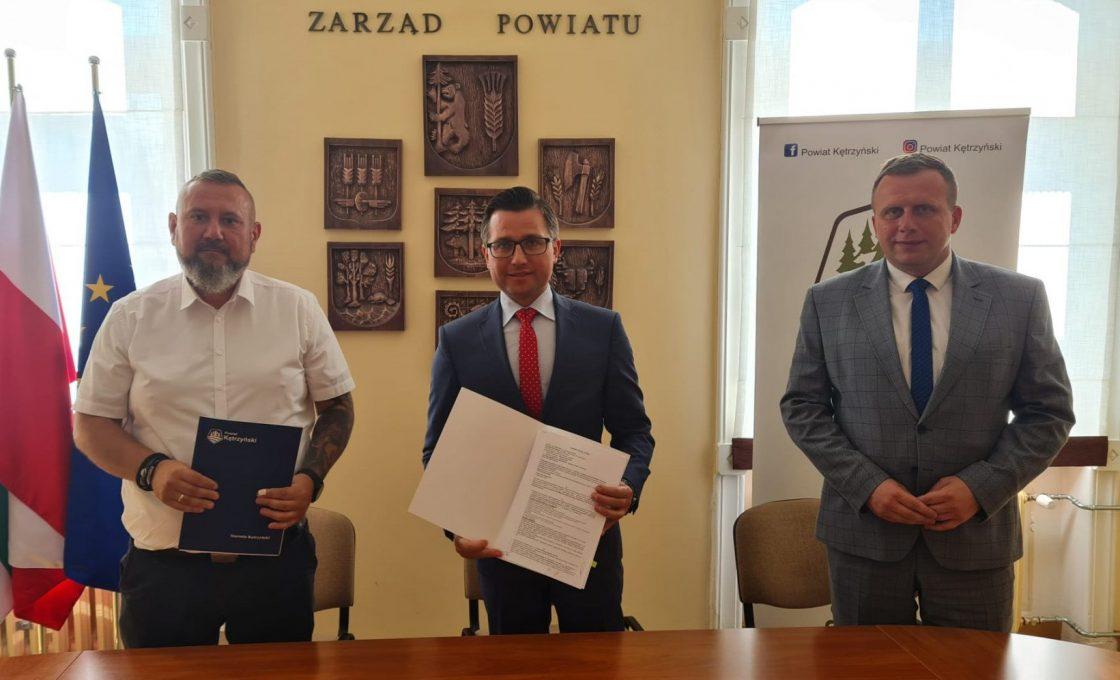 Zdjęcie przedstawia od lewej strony przedstawiciela wykonawcy Pana Marka Kropiwnickiego, starostę kętrzyńskiego Michała Kochanowskiego oraz wicestarostę Andrzeja Lewandowskiego prezentujących podpisaną umowę