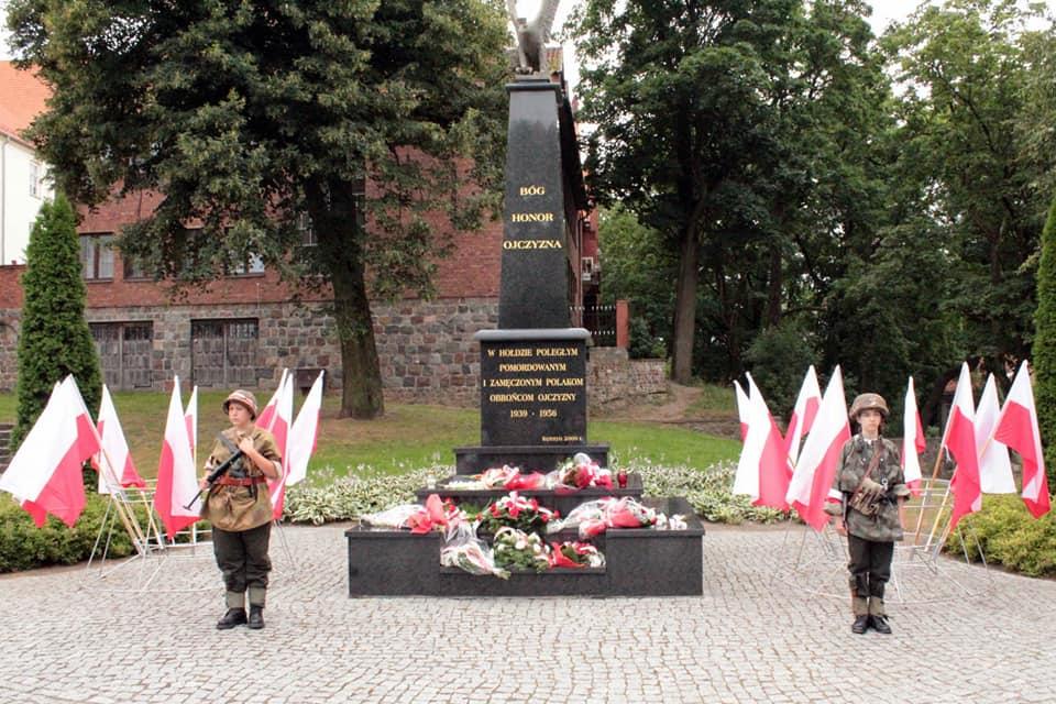 zdjęcie przedstawia dzieci w przebraniach powstańców warszawskich pod pomnikiem