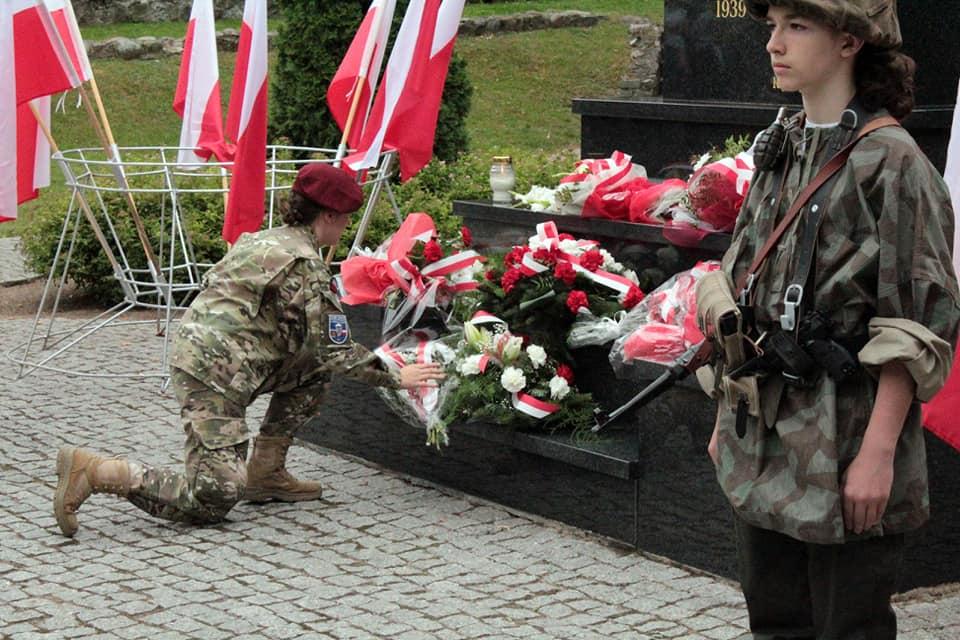 Zdjęcie przedstawia ucznia składającego kwiaty pod pomnikiem