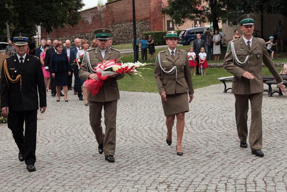 Zdjęcie przedstawia delegacje z kwiatami