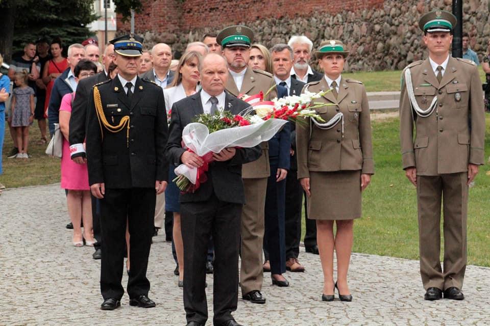 Zdjęcie przedstawia przedstawicieli różnych organizacji w szeregu przed pomnikiem