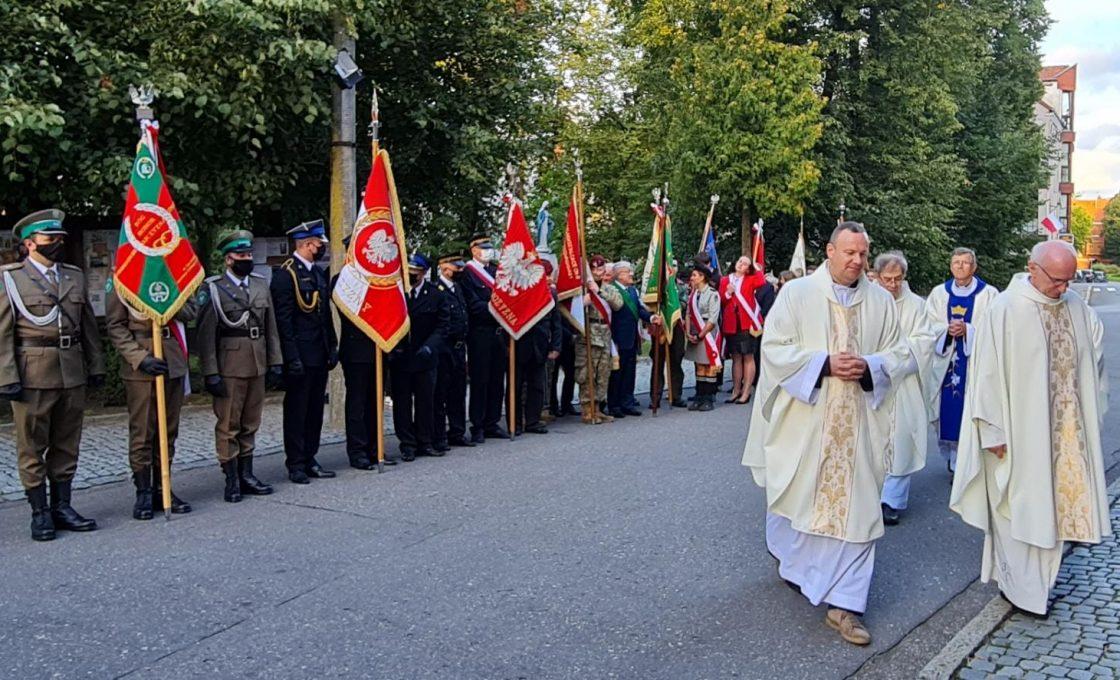 Zdjęcie przedstawia poczty sztandarowe biorące udział w uroczystości przed kościołem