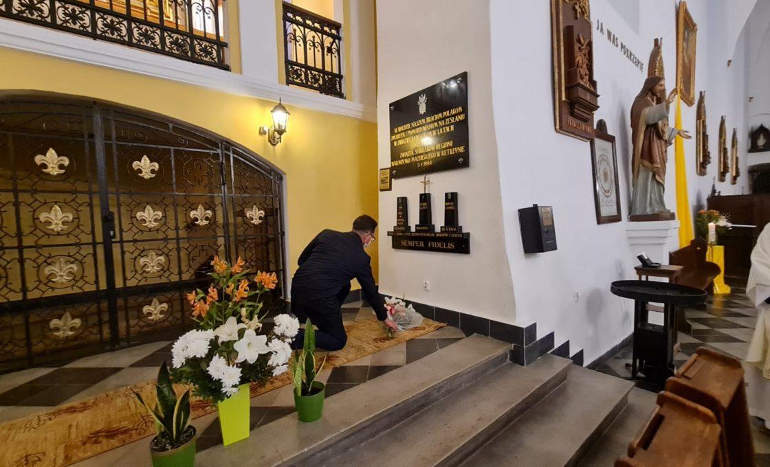 Zdjęcie przedstawia starostę kętrzyńskiego składającego wiązankę kwiatów