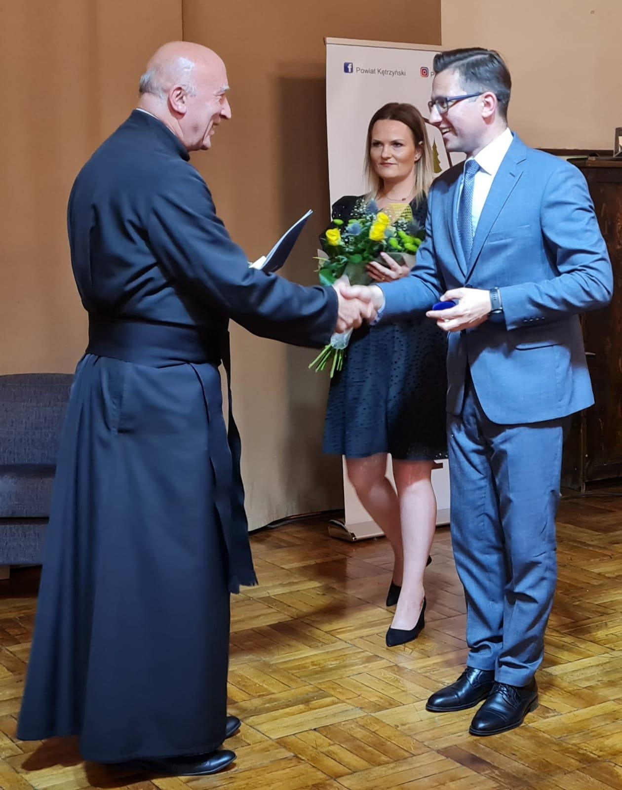 zdjęcie przedstawia laureta Ks. Aleksandra Jacyniaka, Starostę Michała Kochanowskiego, oraz konferansjera uroczystości
